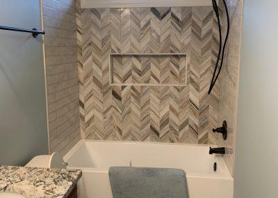 Custom bath and herringbone tiled wall